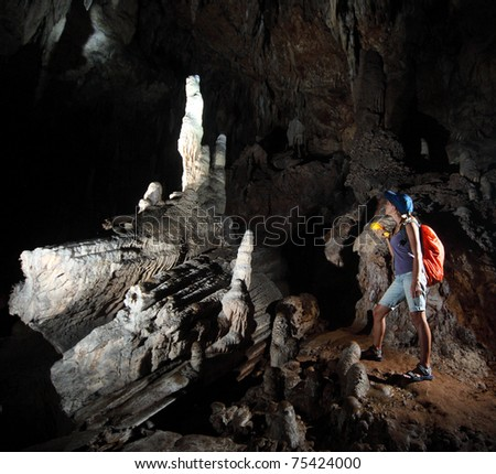 Young woman with backpack exploring huge cave with torch