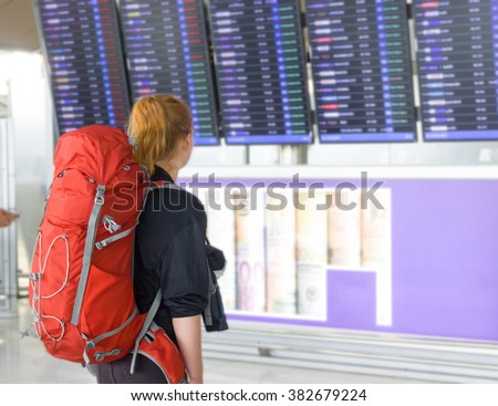 Young woman with backpack in airport near flight timetable