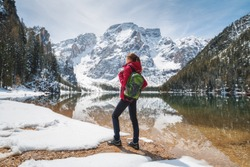 Young woman with backpack on the snowy shore of Braies lake with clear water at sunny bright day in spring. Travel. Landscape with slim girl, reflection in water, mountains, green trees, blue sky