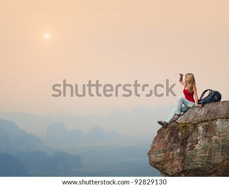 Young woman with backpack sitting on a cliff and enjoying a sunset - stock photo