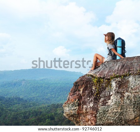Young woman with backpack sitting on a cliff and enjoying a view