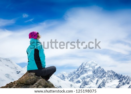 Young woman with backpack sitting on cliff and looking away