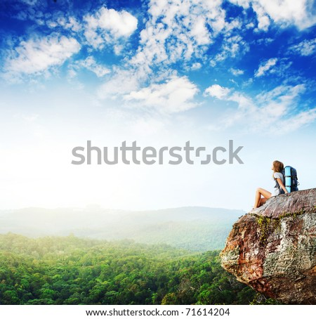Young woman with backpack sitting on cliff and looking to a sky - stock photo