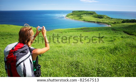 Young woman with backpack standing on a hill with green grass and making snapshot of a beautiful scene
