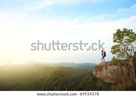 Young woman with backpack standing on cliff's edge and looking to a sky #69934378