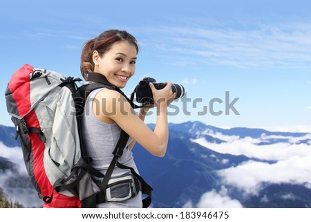 Young woman with backpack taking a photo on the top of mountains, asian