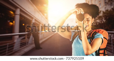 Young woman with backpack taking picture against footbridge against sky in city #737925109