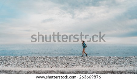 Young woman with backpack walking on beach near the sea. Space for text in left part of the image #263669876