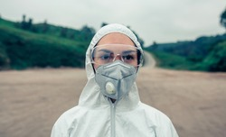 Young woman with bacteriological protection suit and protective mask