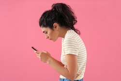 Young woman with bad posture using mobile phone on color background