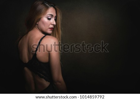 Young woman with bare back on black background #1014859792