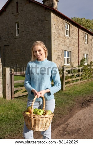 Young woman with basket of apples