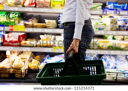 young woman with basket walking in supermarket