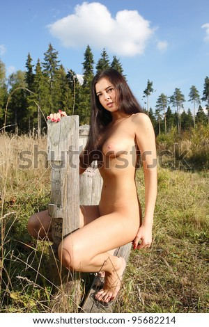 Young woman with beautiful breasts in the forest.