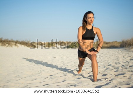 Stock Photo Young woman with beautiful fit body in sportswear stretching legs with lunge hamstring stretch exercise on beach.