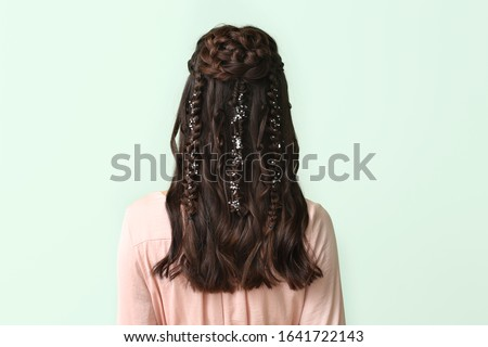 Young woman with beautiful hairdo on color background