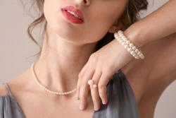 Young woman with beautiful pearl jewelry on light background, closeup