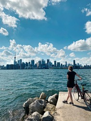 Young woman with bicycle enjoying cityscape view on Toronto city in Canada. Sport summer activity in modern large town. Canadian Toronto islands landmark. Sunny day nature Ontario.