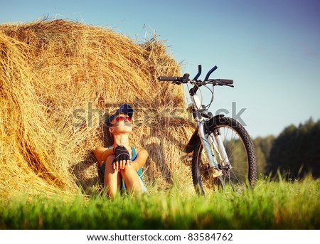 Young woman with bicycle sitting near straw heap and looking to a sky