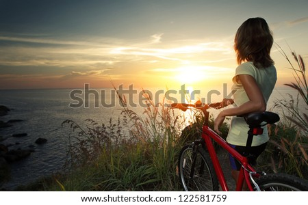 Young woman with bicycle standing on ground and enjoying sunset over sea