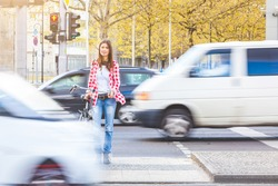 Young woman with bicycle waiting to cross the street at red signal in Berlin. There are blurred cars passing in front of her and behind. Urban lifestyle and travel concepts.