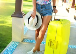 Young woman with big luggage at airport happy of her vacation at warm country on holidays.tanned girl with large suitcases in the airport,holding straw hat,pink sunglasses,tropical elegant and sexy