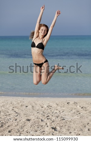 Young woman with bikini girl jumping at the beach with blue sky on the sea in summer vacation