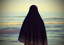 young woman with black dress covering her hair by the calm sea with old toned effect