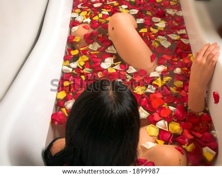 young woman with black hair enjoying rose petal bath in a victorian style bath