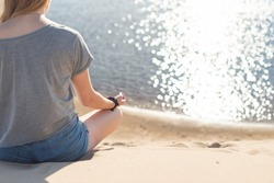 young woman with blond hair practices yoga on the beach against the background of the sea. The woman is sitting in the lotus position on the sand. The glare of the sun is reflected on the water.
