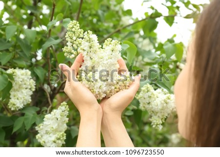 Young woman with blossoming lilac outdoors on spring day #1096723550