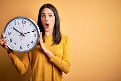 Young woman with blue eyes doing countdown holding big clock over yellow background scared in shock with a surprise face, afraid and excited with fear expression