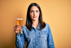 Young woman with blue eyes drinking glass of beer standing over isolated yellow background with a confident expression on smart face thinking serious