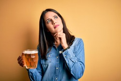 Young woman with blue eyes drinking jar of beer standing over isolated yellow background with hand on chin thinking about question, pensive expression. Smiling with thoughtful face. Doubt concept.