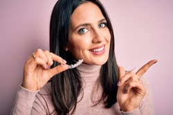 Young woman with blue eyes holding clear aligner standing over pink background very happy pointing with hand and finger to the side