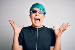 Young woman with blue fashion hair wearing thug life sunglasses over white background celebrating mad and crazy for success with arms raised and closed eyes screaming excited. Winner concept