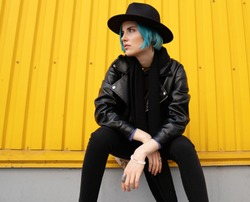 Young woman with blue hair in a black leather jacket and hat sits near an orange wall