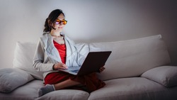 Young woman with blue light blocking glasses (yellow lenses) working with laptop on white sofa