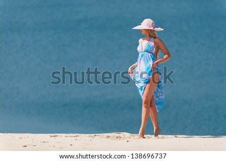 young woman with blue water on the white sand in the pink hat #138696737