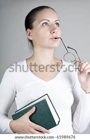 Young woman with book and glasses, thoughtfully looking up, on gray background