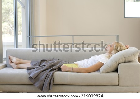 Young woman with book asleep on sofa, profile