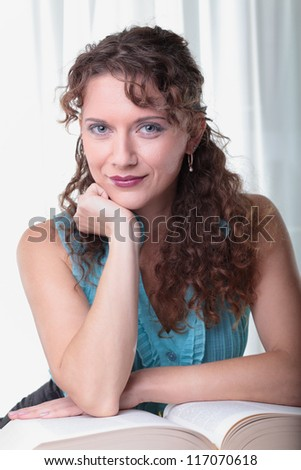 Young woman with book on white background.