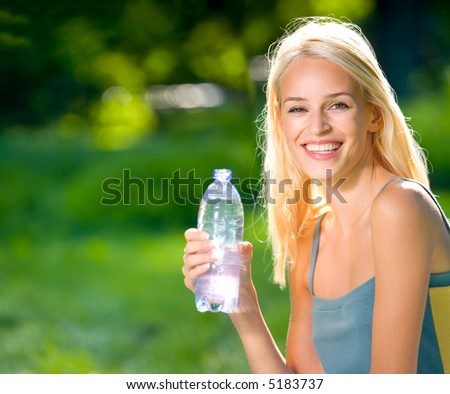 Young woman with bottle of water outdoors. To provide maximum quality I have made this image by combination of two photos.