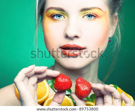 Young woman with bright make-up and with fruits