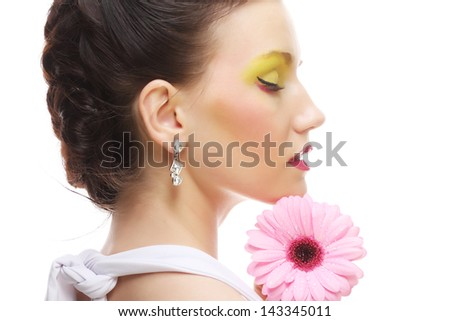 Young woman with bright make up holding pink gerber