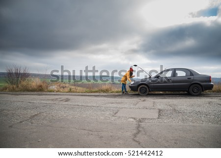young woman with broken car in the middle of the road