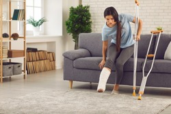 Young woman with broken leg in plaster cast trying to stand up from sofa and walk with crutches in living-room. Physical injury, bone fracture, car or home accident, rehabilitation of people concept
