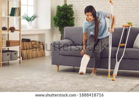 Young woman with broken leg in plaster cast trying to stand up from sofa and walk with crutches in living-room. Physical injury, bone fracture, car or home accident, rehabilitation of people concept Stock photo ©