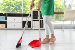 Young woman with broom and dustpan cleaning in office