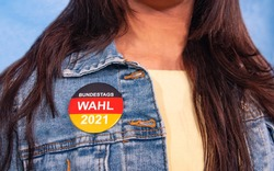 Young woman with brown hair and an election button for the German federal election on their Jeans jacket , with the inscription: